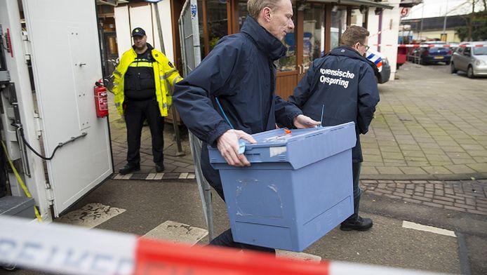 Het hoofd wordt in een verzegelde plastic doos weggehaald door medewerkers van de Forensische Opsporing