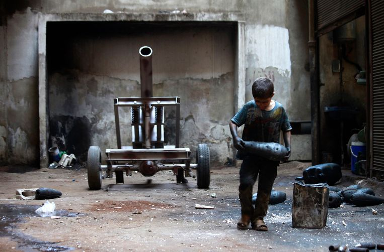 Issa, 10 years old, carries a mortar shell in a weapons factory of the Free Syrian Army in Aleppo, September 7, 2013. Issa works with his father in the factory for ten hours every day except on Fridays. REUTERS/Hamid Khatib (SYRIA - Tags: POLITICS CONFLICT CIVIL UNREST TPX IMAGES OF THE DAY) Beeld REUTERS