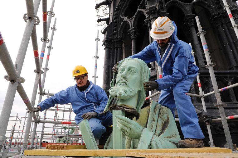 Medewerkers van een restauratiebedrijf verwijderen het beeld van de apostel Andreas van de Notre-Dame. Beeld AFP