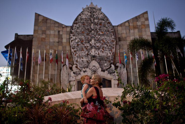 Een vrouw kust een kind bij het monument ter nagedachtenis aan de aanslagen op Bali in 2002, waarbij 202 mensen om het leven zijn gekomen, onder wie 88 Australische toeristen.  Beeld Getty Images