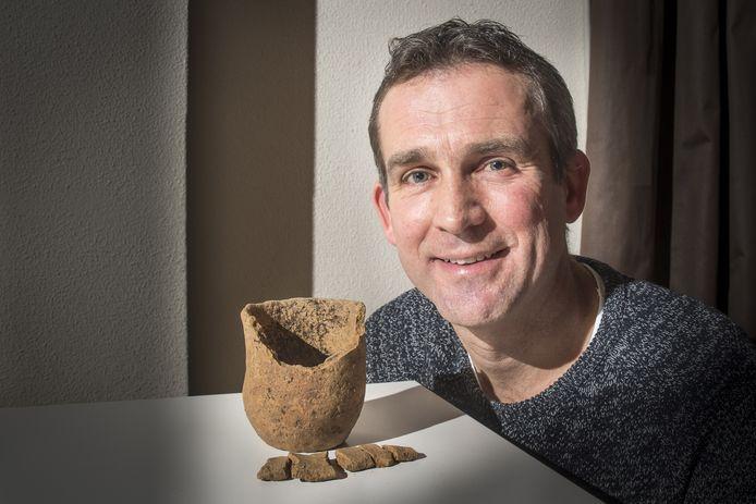 Archeoloog Jeroen Flamman met beker van aardewerk, die bij de aanleg van de nieuwe N18 is opgegraven.