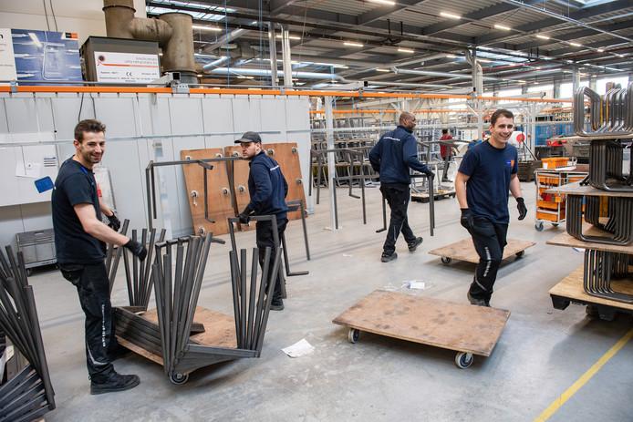 In een nieuwe productiehal van EromesMarko hangen medewerkers frames van lestafels aan de lijn die ze naar een spuitcabine voert.