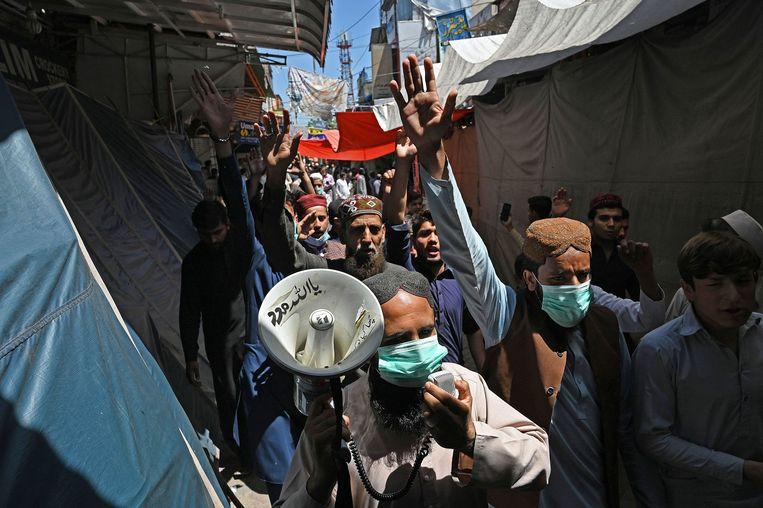 Handelaren in de Pakistaanse stad Lahore betuigen steun aan de radicaal-islamitische partij TLP. De leider van de TLP eiste dat de Franse ambassadeur wordt uitgewezen. Beeld AFP