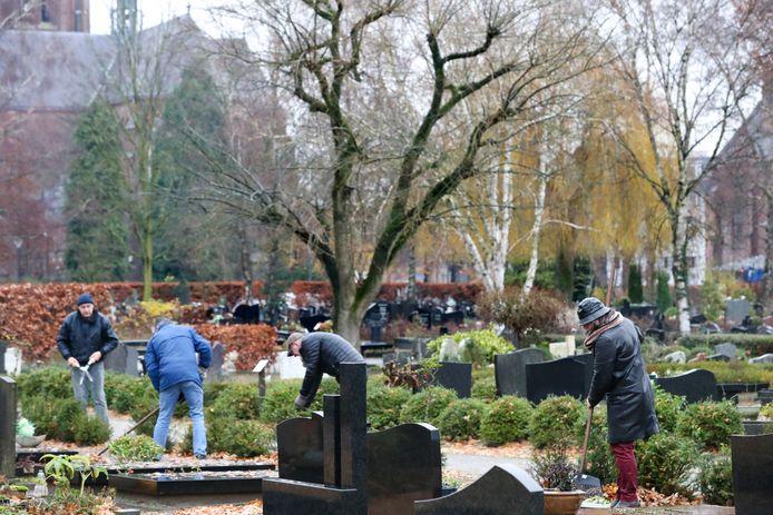 AnneMarie van Schoonderwalt, beheerster van het kerkhof  in Best en tuinmannen druk doende om het kerkhof mooi en schoon te houden.