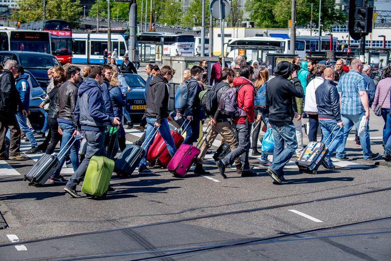 Voorbijgangers met rolkoffers in de binnenstad van Amsterdam. Beeld ANP