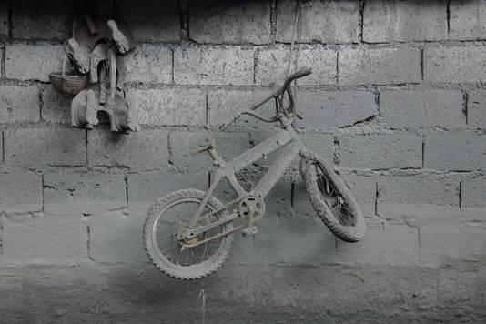 Een fiets, dik onder de as, is een stille getuige van de vulkaan uitbarsting.