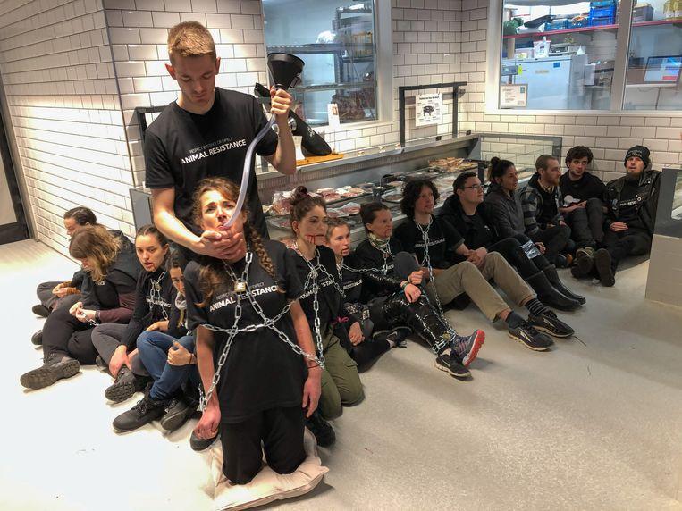 De dierenactivisten van Animal Resistance lieten zich zondag vastketenen in de Antwerpse versmarkt Cru. Beeld Marc De Roeck