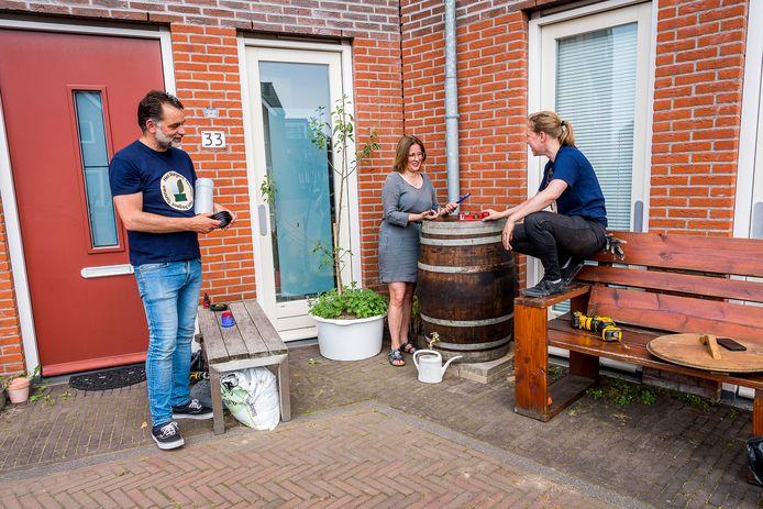 Tijs van Ruth en Emma Gerritse (rechts) helpen onder anderen bewoonster Jikke Vergragt aan een regenton op het V.O.C.-Plein in Rotterdam-Delfshaven.