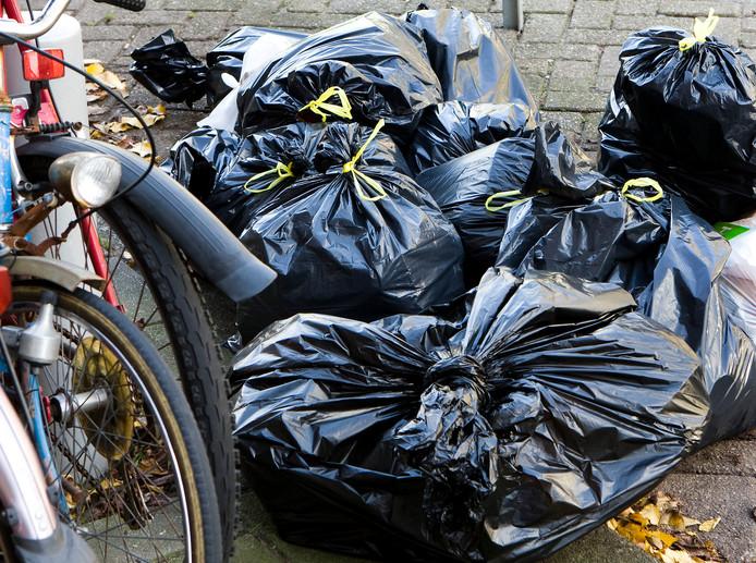 Foto ter illustratie van afvalzakken op straat.