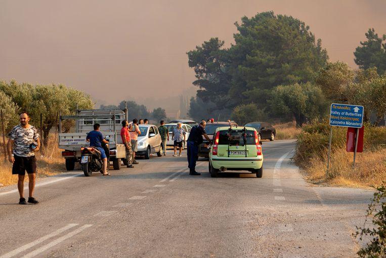 Toeristen en inwoners kijken naar een natuurbrand in de regio Kalamonas op Rodos. Beeld EPA