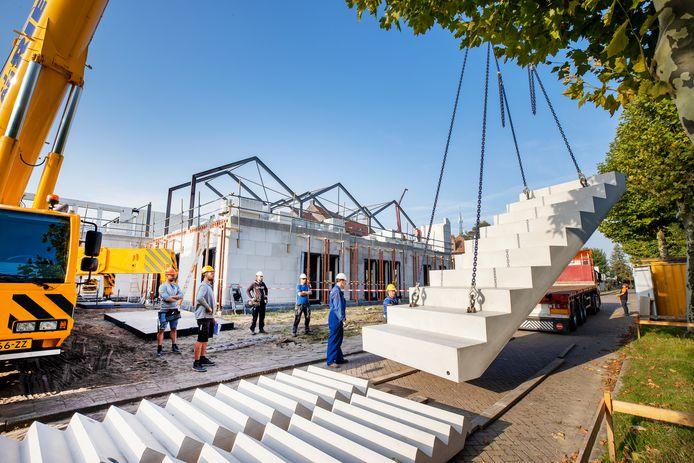 Met een grote hijskraan worden een aantal trappen in de nieuwe MFA Hart van Hapert geplaatst.