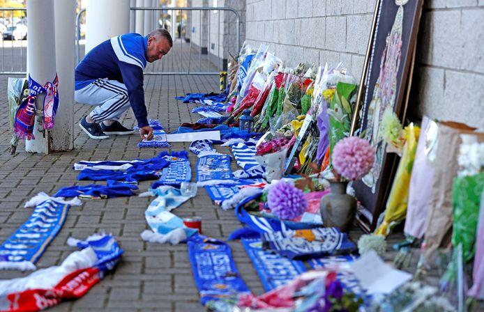 Een Leicester City-fan legt een sjaal bij het voetbalstadion nadat bekend is geworden dat clubeigenaar Vichai Srivaddhanaprabha is omgekomen bij de heli-crash.