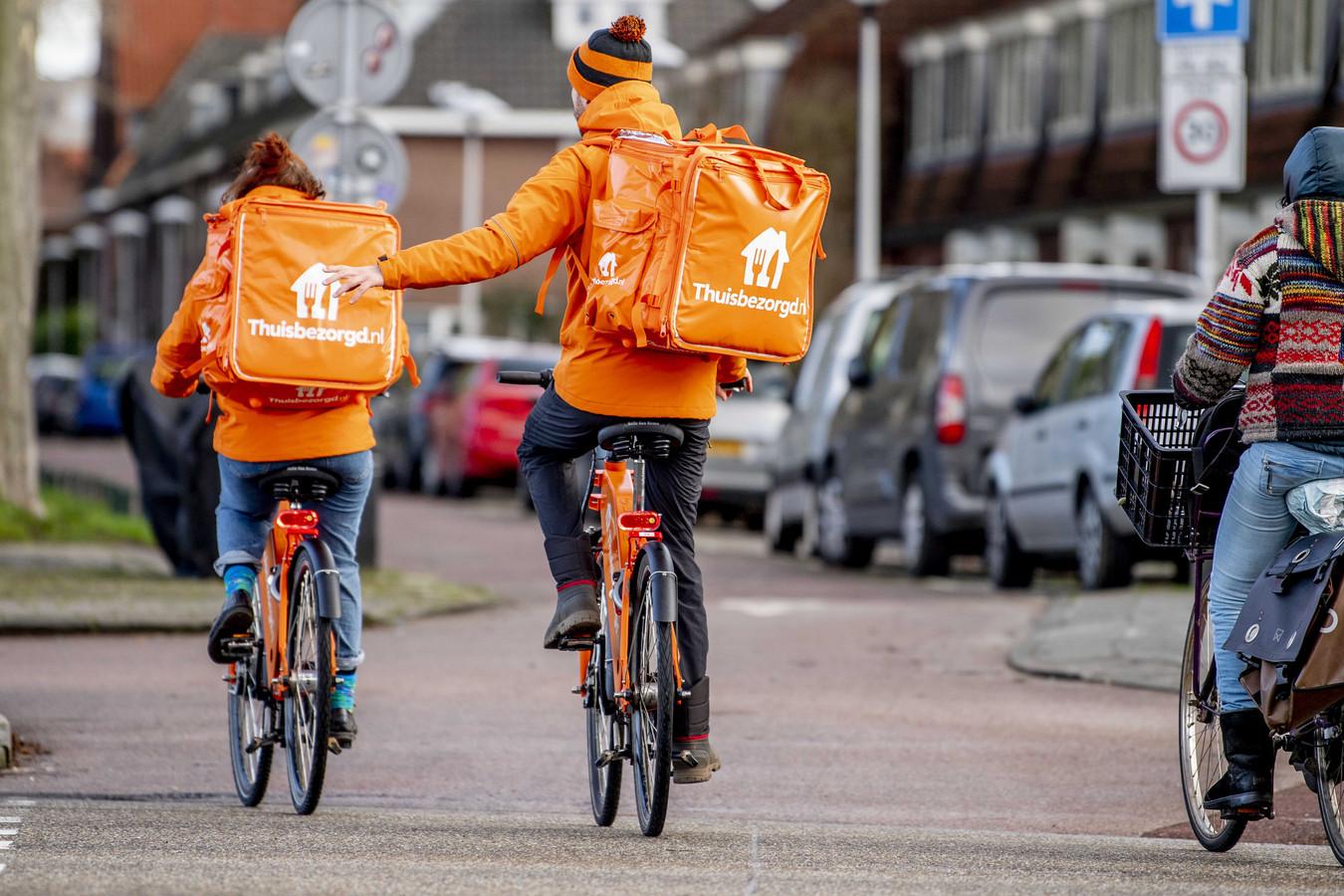Maaltijdbezorgers van Thuisbezorgd onder weg op hun fiets.