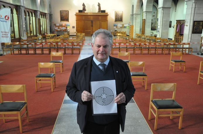 Deken Henk Laridon in de Heilige Familiekerk met een voorbeeldje van zo'n labyrint. Dat labyrint vervangt het rode tapijt achteraan de kerk.