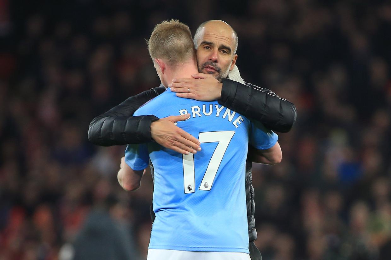 Pep Guardiola, de Spaanse succestrainer van Manchester City, omhelst zijn Belgische sterspeler Kevin De Bruyne. Beeld Getty