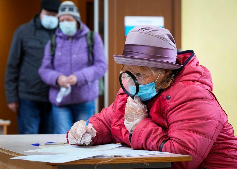 Een vrouw vult haar stembiljet voor de Russische parlementsverkiezingen in bij een stembureau in Sint-Petersburg. Beeld AP
