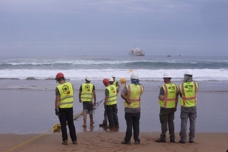 Werknemers observeren een glasvezelkabel van een kabellegschip op het strand van Arrietara, nabij Bilbao, Noord-Spanje.