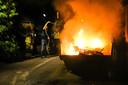 Een bewoner doet met een tuinslang het nodige voorvwerk voor de brandweer in een fikkende grofvuil-container.