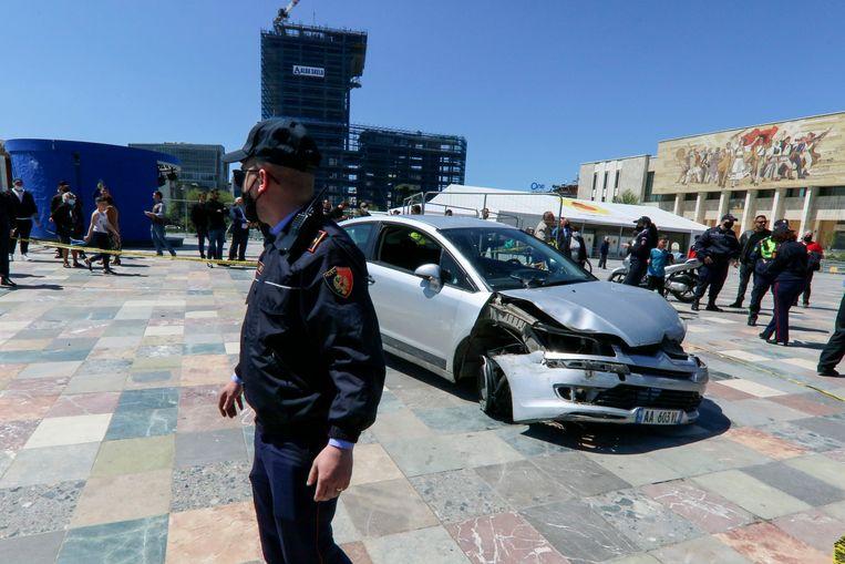 Een agent na het beschadigde voertuig op het centrale Skanderberg-plein.   Beeld AP