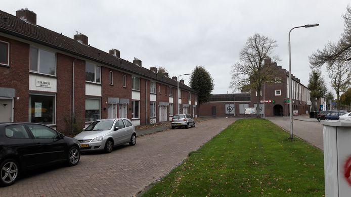 De woningen links maken plaats voor een appartementencomplex voor senioren tegen de achtergrond van het buurtwinkelcentrum.