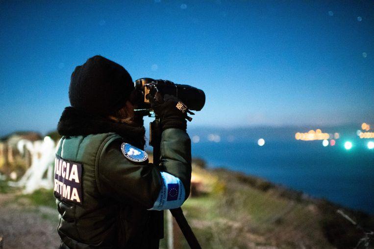 Een medewerker van Frontex houdt de Griekse kust bij Molyvos in de gaten.  Beeld Isopix