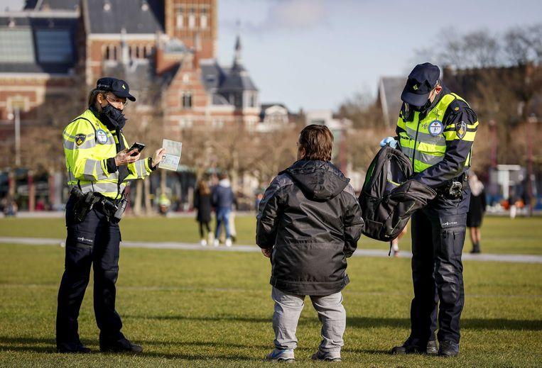 Politieagenten fouilleren een man tijdens een coronaprotest op het museumplein. Vanaf woensdag fouilleert de politie preventief in vijf wijken om wapenbezit tegen te gaan.  Beeld ANP