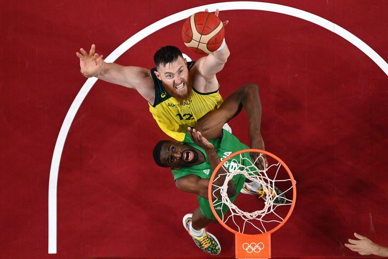 De Australiër Aron Baynes (top) gaat naar de basket terwijl de Nigeriaanse Ekpe Udoh reageert in de basketbalwedstrijd van de mannen voorronde groep B tussen Australië en Nigeria in de Saitama Super Arena in Saitama op 25 juli 2021.  Beeld AFP