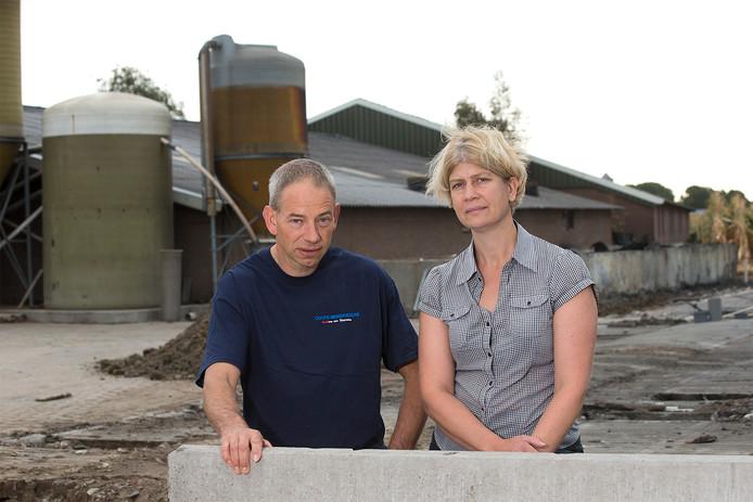Rudi en Hetty Krüs naast de resten van de afgebrande stal en voor de oudere stal waar nog zo'n 1200 varkens in staan.