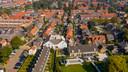 Het huidige kerkgebouw van de Gereformeerde Gemeente in Nederland aan de Kerkstraat in Alblasserdam (wit, in het midden van de foto) is te klein.