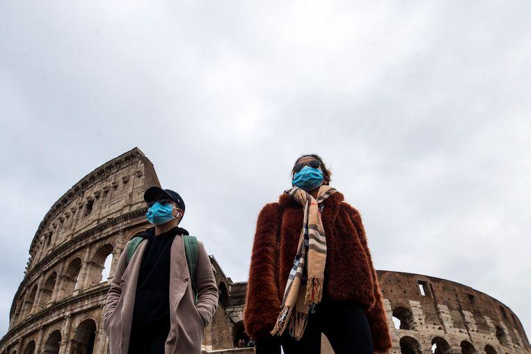 Toeristen voor het Colosseum in Rome dragen een gezichtsmasker.   Beeld EPA
