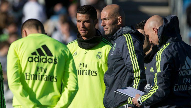 Zinédine Zidane met Cristiano Ronaldo en assistent David Bettoni (rechts). Beeld AP