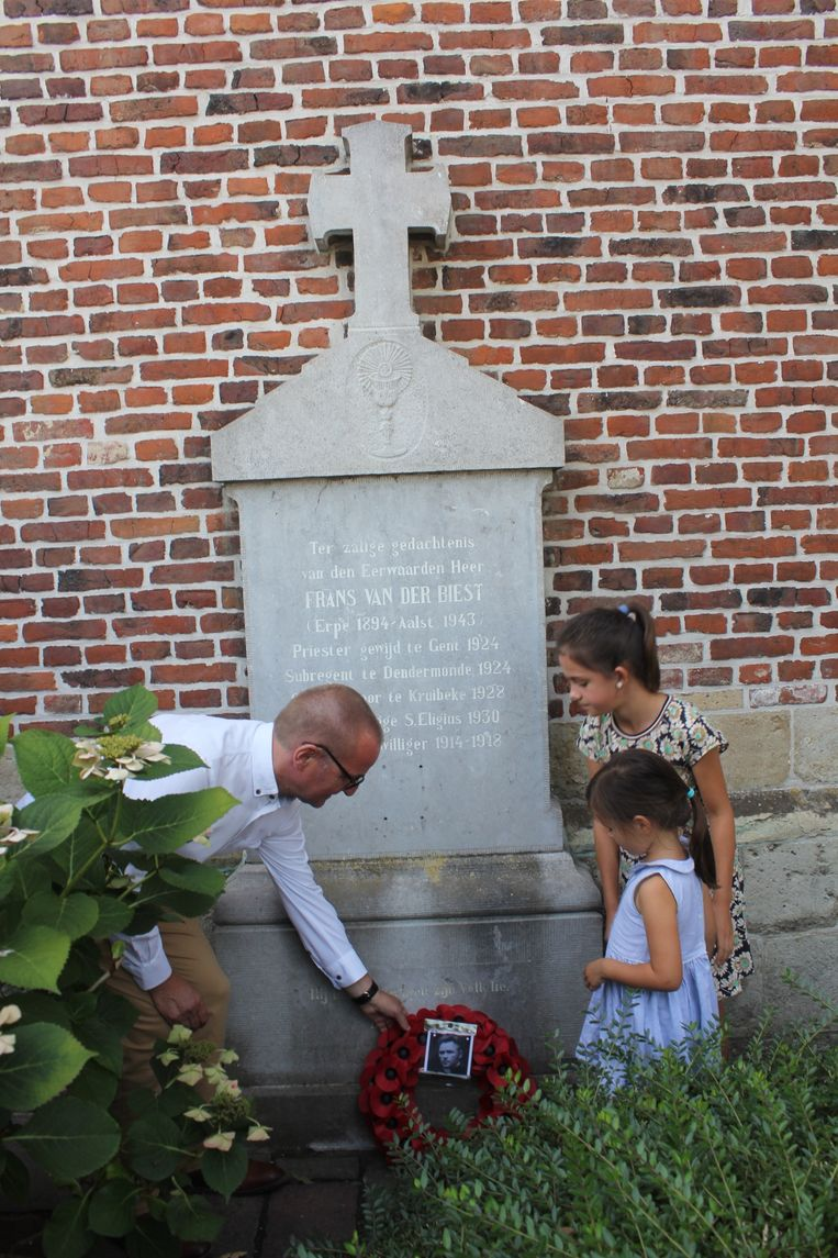 De familie van Frans Van Der Biest legt een krans klaprozen neer bij zijn graf aan de kerk van Erpe.