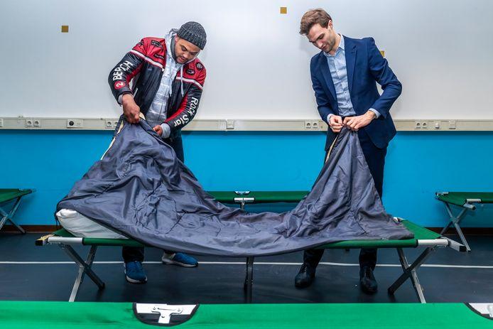 Wethouder Maarten van Ooijen helpt een dakloze met het opmaken van zijn bed in de daklozenopvang Stadhuisbrug. Nu luidt Van Ooijen samen met drie andere wethouders van Amsterdam, Rotterdam en Den Haag de noodklok.