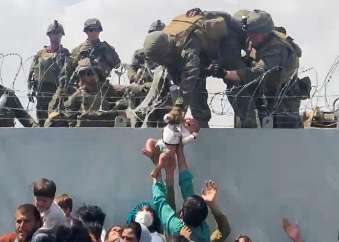 Een baby wordt overgedragen aan Amerikaanse soldaten op de luchthaven van Kaboel.