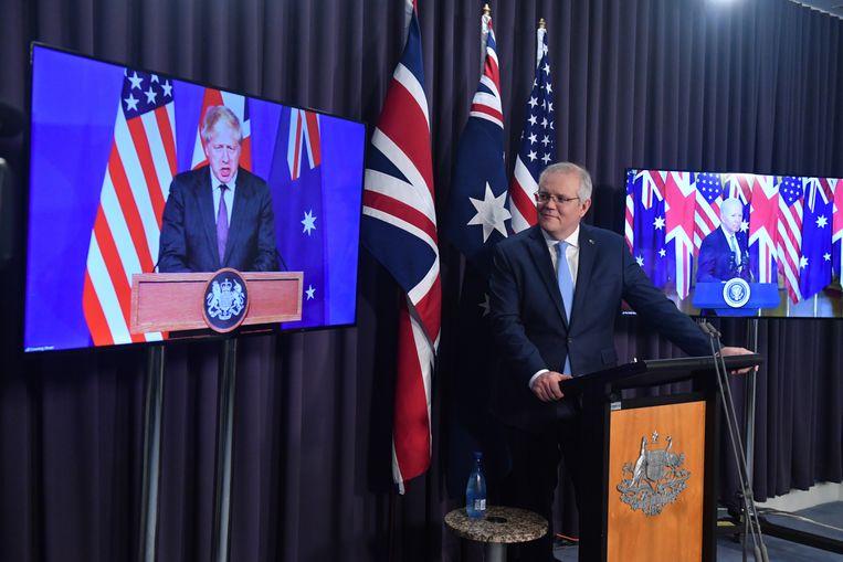 De Australische premier Scott Morrison met op de beeldschermen achter zich Boris Johnson (links) en Joe Biden, bij de bekendmaking van het nieuwe Aukus-pact.  Beeld EPA