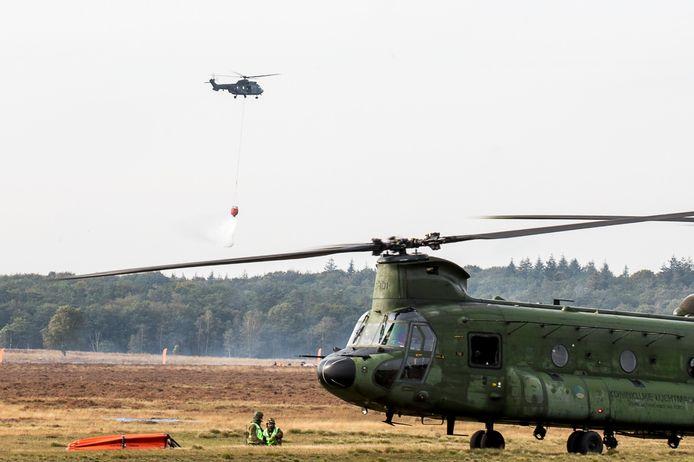 De Cougar-helikopter lost water op de Ginkelse Heide. Op de voorgrond de Chinook.