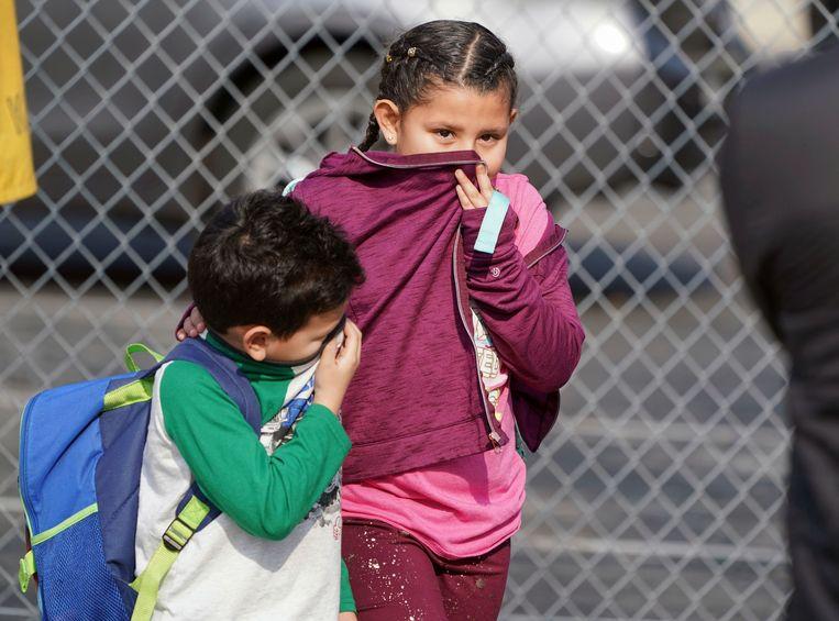 Schoolkinderen van basisschool Park Avenue in Cudahy bedekken hun neus en mond nadat de brandstof is neergedaald op de school en omgeving.  Beeld AP