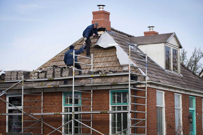 Archiefbeeld: Bouwvakkers herstellen aardbevingsschade aan een schoorsteen van een huis in het Groningse dorp 't Zandt.