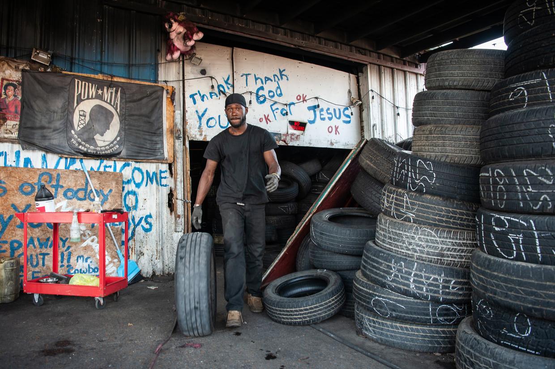 Een werknemer in een handel in tweedehands autobanden.  Door de vele gaten in de wegen slijten de banden extra snel in Mississippi. Beeld Rory Doyle