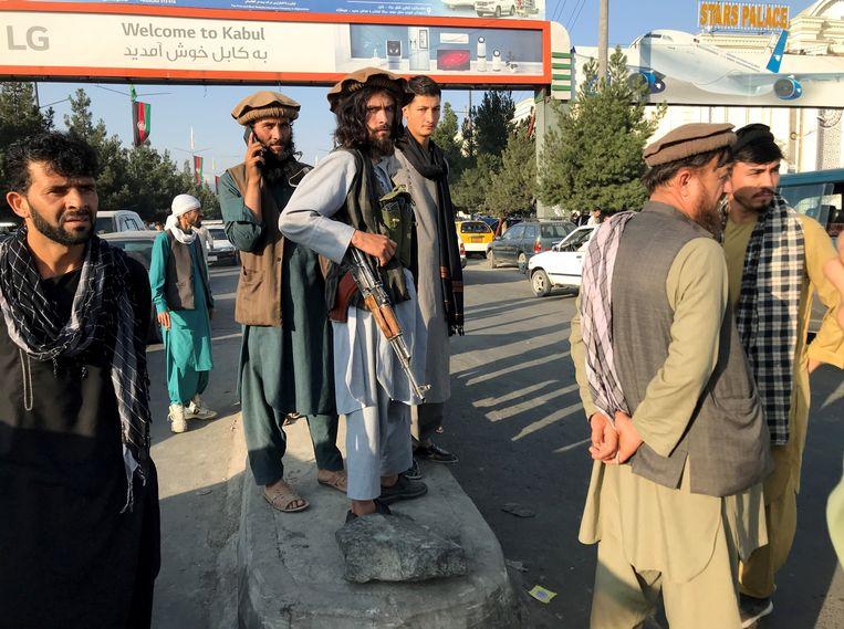 Talibanstrijders bij het vliegveld van Kaboel.  Beeld REUTERS
