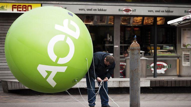 Maart vorig jaar: Een medewerker van de AOb blaast een ballon op bij de Amsterdam Arena voor het protest van de onderwijsbonden tegen de voorgenomen bezuinigingen in het passend onderwijs. Beeld anp