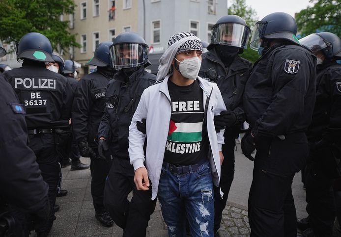 Een betoger wordt weggeleid in Berlijn.