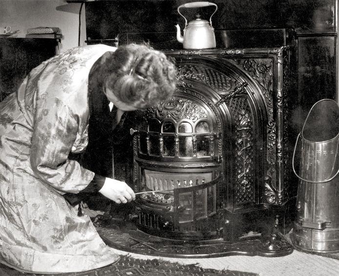 Kolenkachel. Vrouw in ochtendjas hurkt naast de  haard en prikt met een pook in de brandende kolen, om het vuur op te stoken. Op de kachel een waterketel en ernaast een koperen kolenkit.
