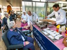 Bejaarde 'Arnhemse meisjes' in de rij voor portie poffertjes, met advocaat en boerenjongens