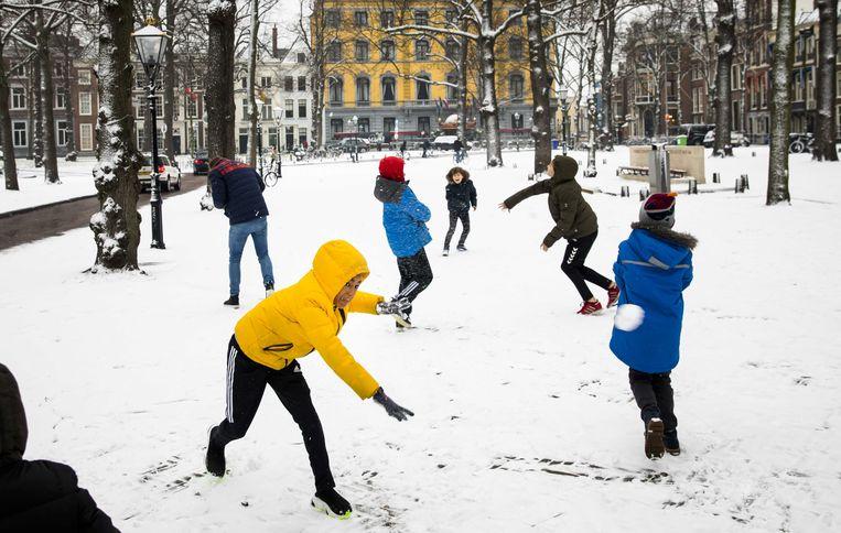 Kinderen gooien met sneeuwballen op het Lange Voorhout in Den Haag. Beeld ANP