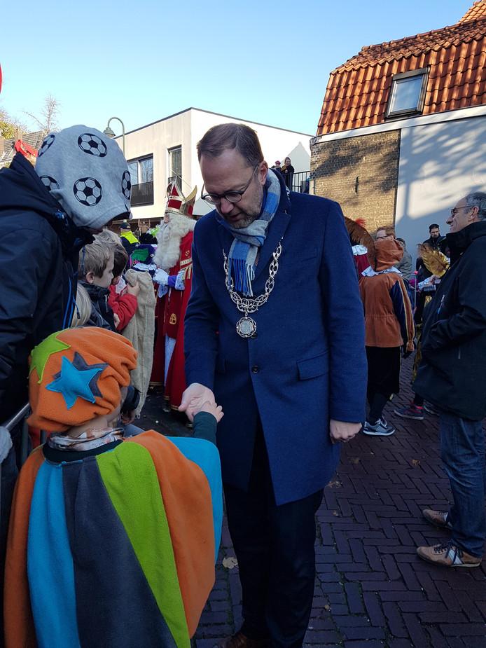 De burgemeester van Gouda krijgt van kleine piet een kruidnootje.
