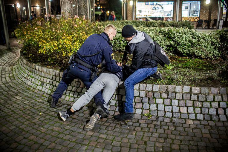 De politie pakt in de wijk Bellevuegård een jongen op. Beeld Julius Schrank / De Volkskrant