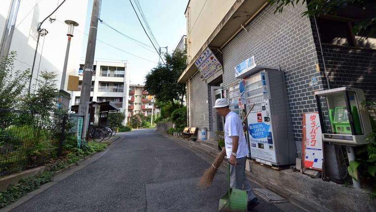 De 79-jarige Kohei Jinno veegt de straat voor zijn winkel en het appartementencomplex waarin hij woont. Beeld AFP