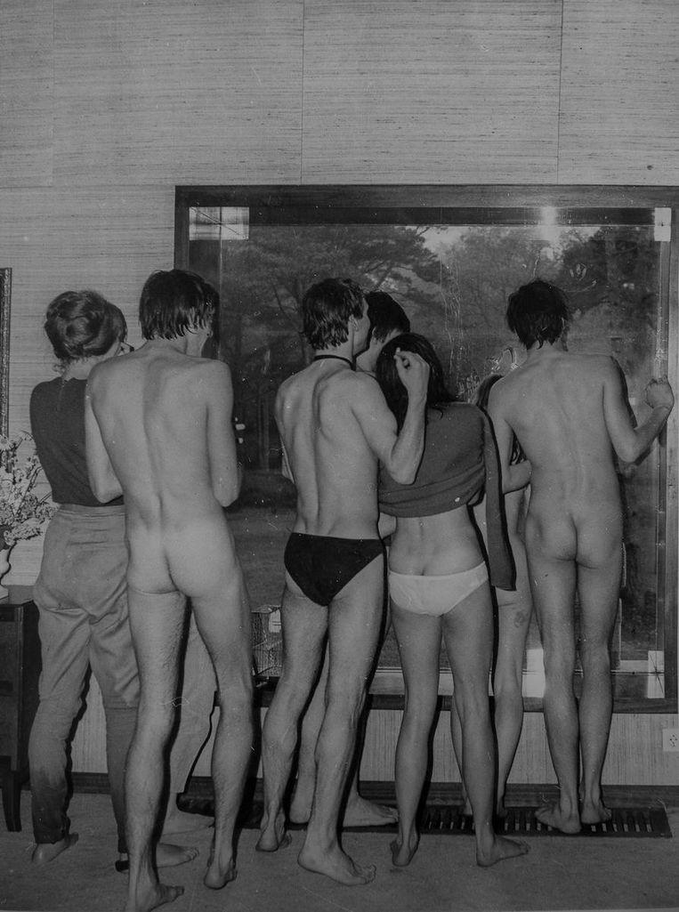 Een groep feestgangers met blote billen voor het raam, net onder de douche vandaan Beeld -