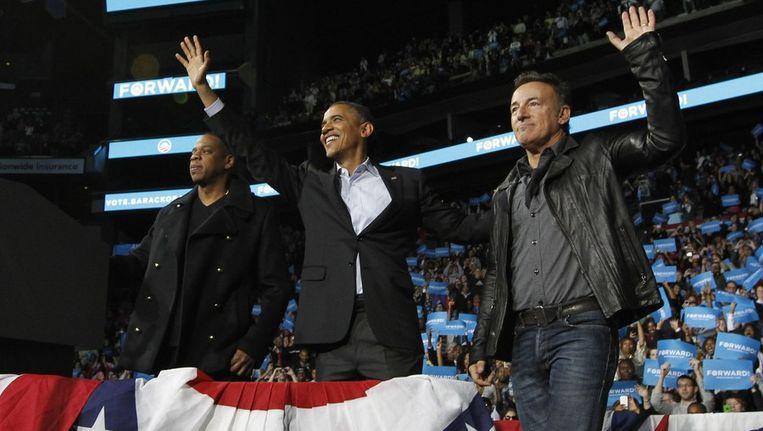 Obama (m) op het podium met rapper JayZ (l) en Bruce Springsteen (r) Beeld reuters